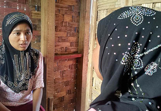 Case worker Ma Hla Khin speaks with a woman who came for GBV counseling at the WGC.
