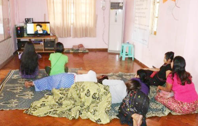 Zin Zin and her peers watch a TV show at a Sex Workers in Myanmar center.