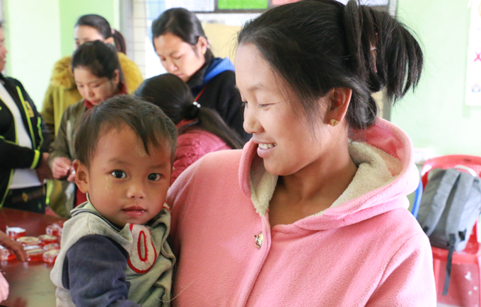 Kawt Phan and her one-year-old son relax in the women-friendly space. The better access women have to information about their health and rights, the better care they can take of themselves and their children.