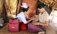 Daw Aye Myint examines a mother and her newborn in Zee Taw Pin Village